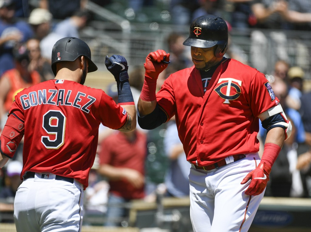 Minnesota Twins designated hitter Nelson Cruz, right, celebrates with Marwin Gonzalezafter hitting a solo home run off a pitch by Seattle Mariners pi