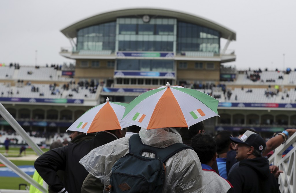 Indian fans wait as it rains before the Cricket World Cup match between India and New Zealand was abandoned at Trent Bridge in Nottingham, England, Th