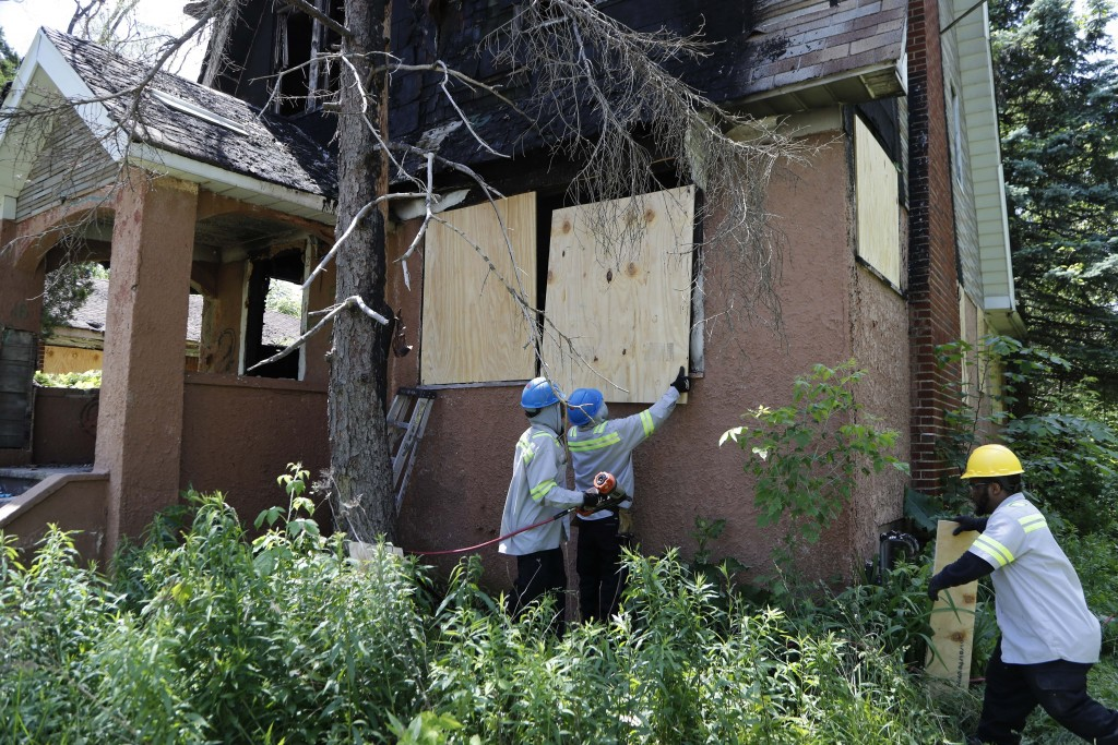 In a photo from Tuesday, June 11, 2019, members of the Detroit's Board Up Brigade board up a vacant home in north Detroit. Hundreds of vacant houses i...