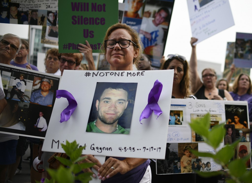 FILE - In this Friday, Aug. 17, 2018 file photo, Christine Gagnon of Southington, Conn. protests with other family and friends who have lost loved one