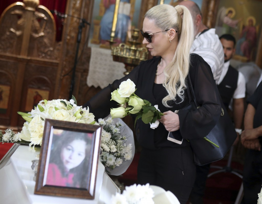 A relative mourns over the coffins of Livia Florentian Bunea, 36, from Romania and her eight year-old daughter Elena Natalia at a church in the villag...