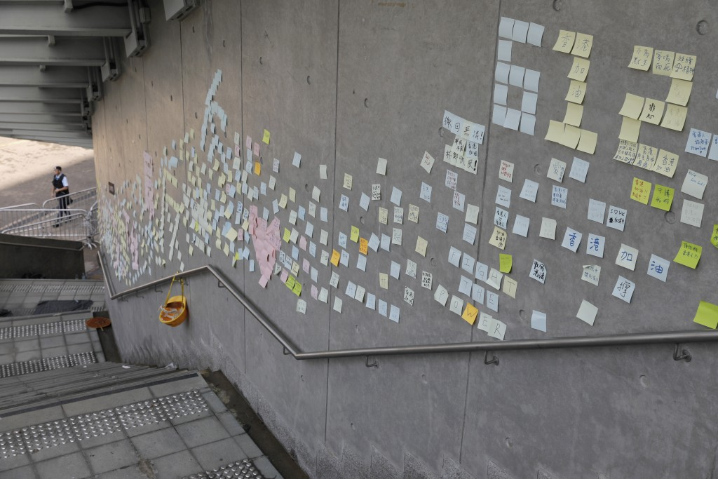 Stickers with messages supporting protesters are left on a wall near the Legislative Council in Hong Kong on Friday, June 14, 2019. Calm appeared to h