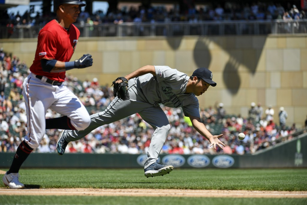 Seattle Mariners pitcher Yusei Kikuchi, right, is too late with the throw to first as Minnesota Twins' Ehire Adrianza, left, runs the baseline after b