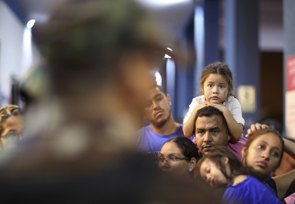 Venezuelan migrants wait in line to pass migration controls before the deadline on new regulations that demand passports from migrants, in Tumbes, Per