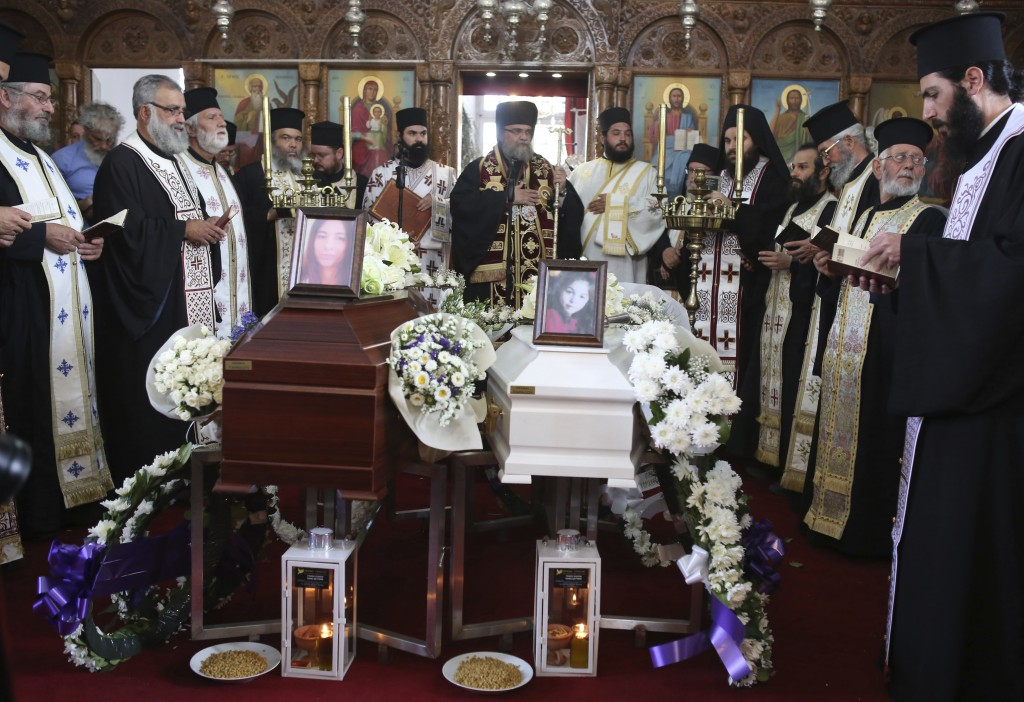 Greek Orthodox Christian clergymen preside over the funeral of Livia Florentian Bunea, 36, from Romania and her eight year-old daughter Elena Natalia