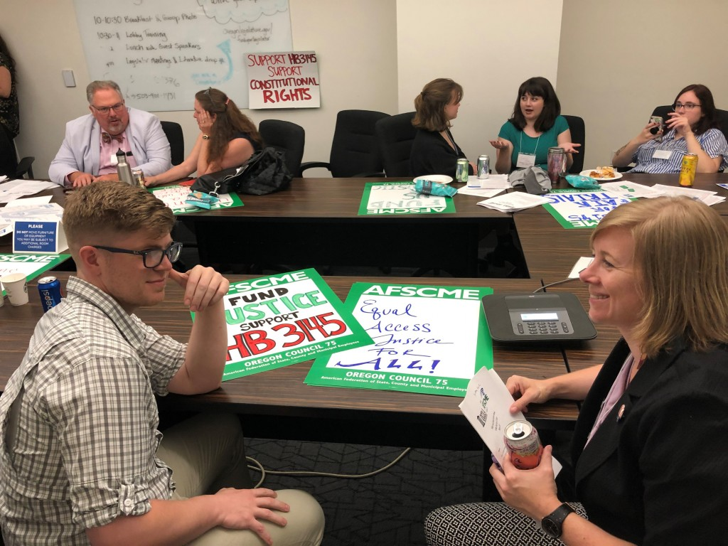 This June 12, 2019 photo public defenders in Oregon strategize at the Oregon Capitol in Salem, Oregon before lobbying lawmakers to pass legislation th...
