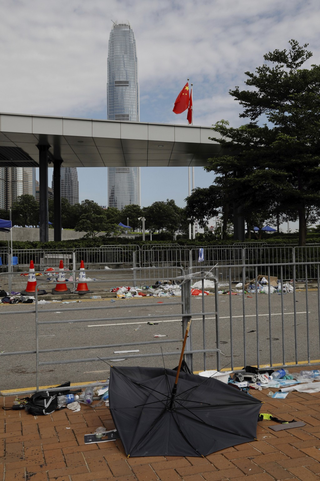 A broken umbrella left in the aftermath of Wednesday's violent protest against proposed amendments to an extradition law is seen near the Chinese flag