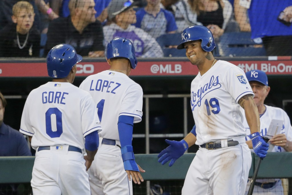 Kansas City Royals' Cheslor Cuthbert (19) greets Terrance Gore and Nicky Lopez at the dugout after the latter two scored on a double by Whit Merrifiel...