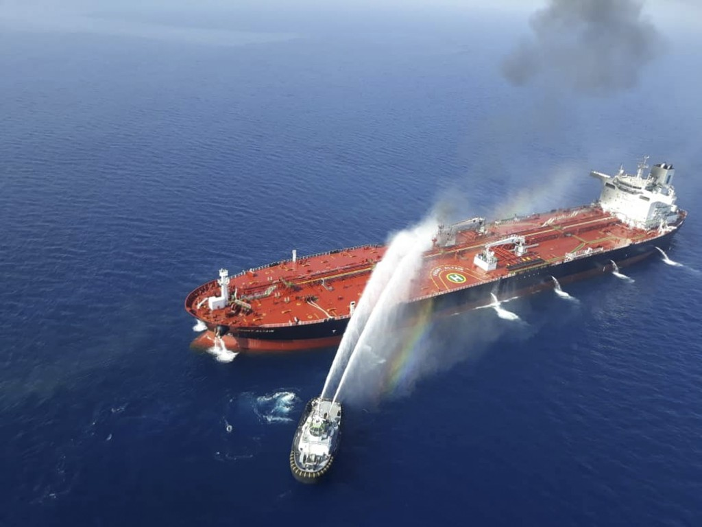 An Iranian navy boat sprays water to extinguish a fire on an oil tanker in the sea of Oman, Thursday, June 13, 2019. Two oil tankers near the strategi