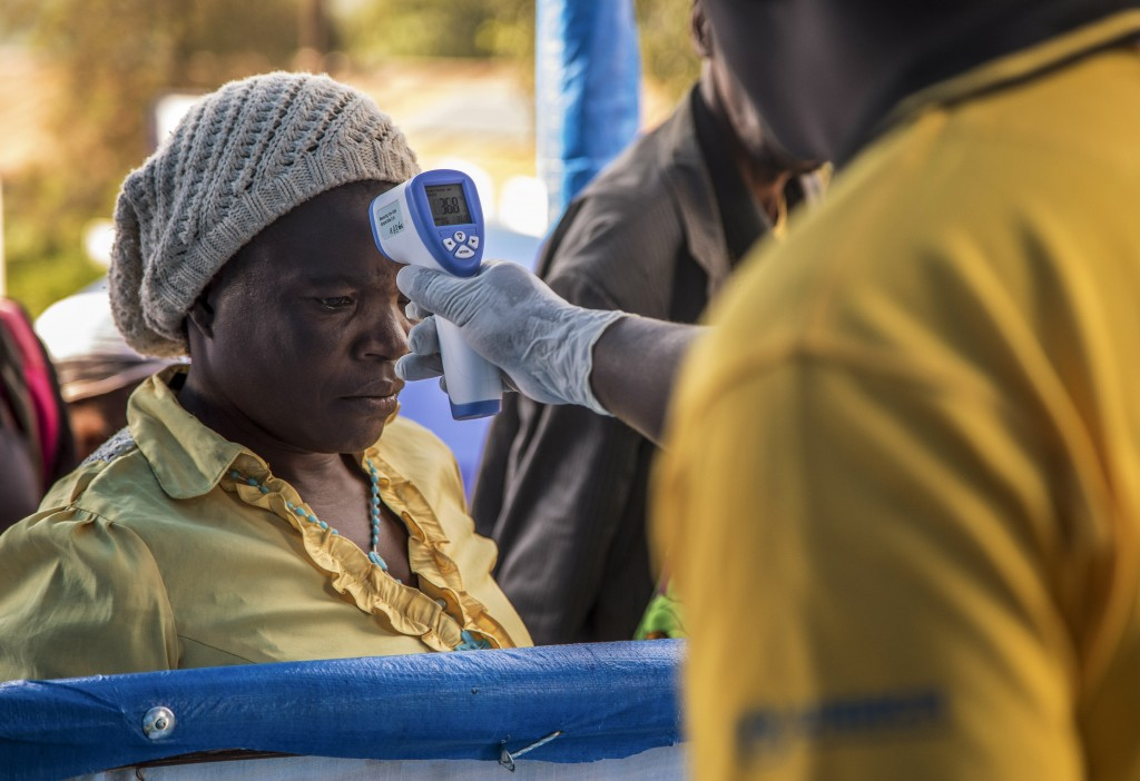 In this photo provided by the International Rescue Committee, a Congolese refugee is screened for Ebola symptoms at the IRC triage facility in the Kya