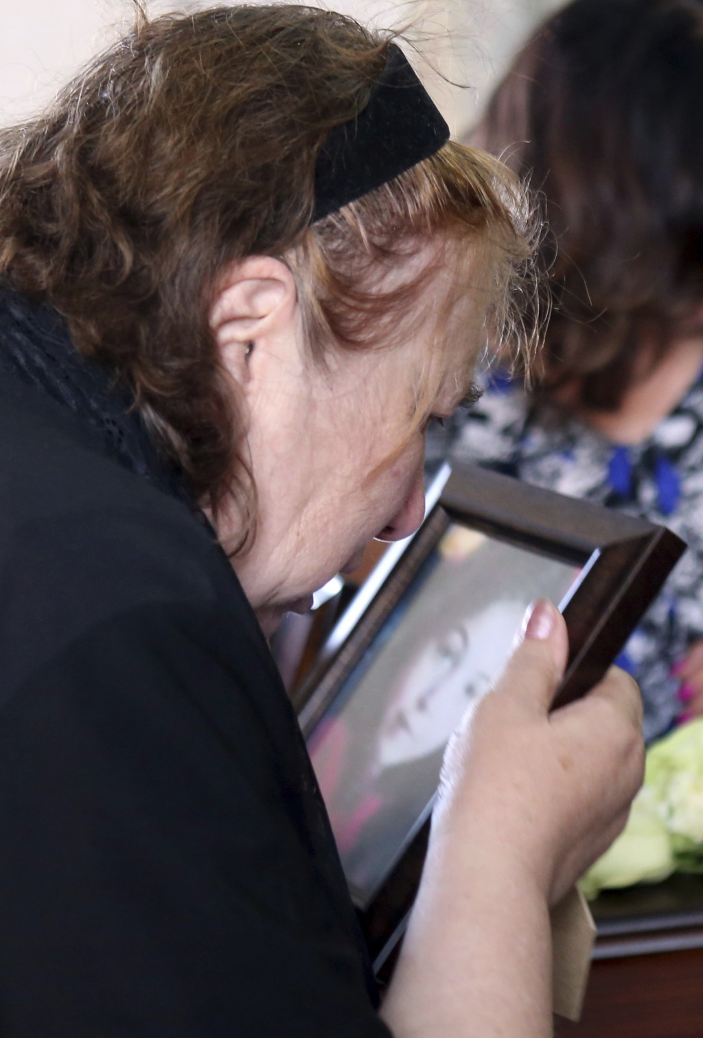 The grandmother of eight year-old Elena Natalia Bunea leans over to kiss a photograph of the child during the funeral of the girl and her mother Livia