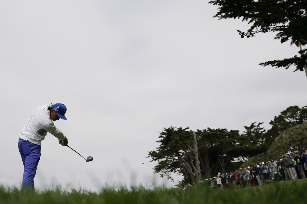 Rickie Fowler hits his tee shot on the 14th hole d...