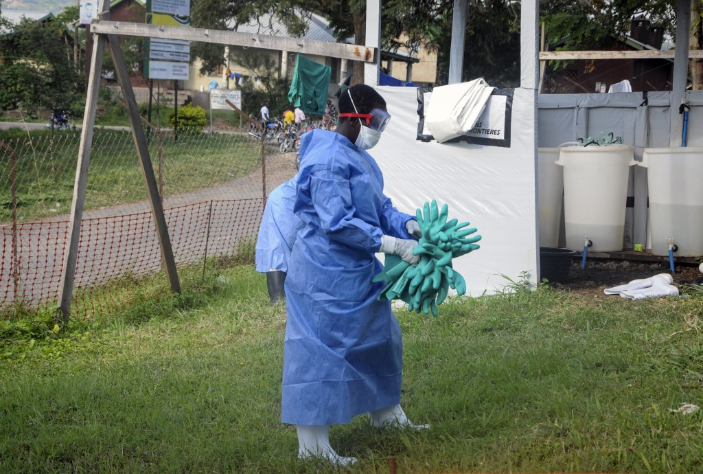 A medical worker carries a bunch of protective rubber gloves used to prevent infection, at the hospital where the first cross-border Ebola victim was