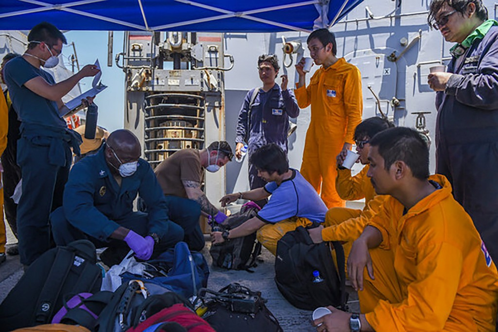 In this June 13, 2019, photo released by the U.S. Navy, sailors aboard the Arleigh Burke-class guided-missile destroyer USS Bainbridge render aid to t...