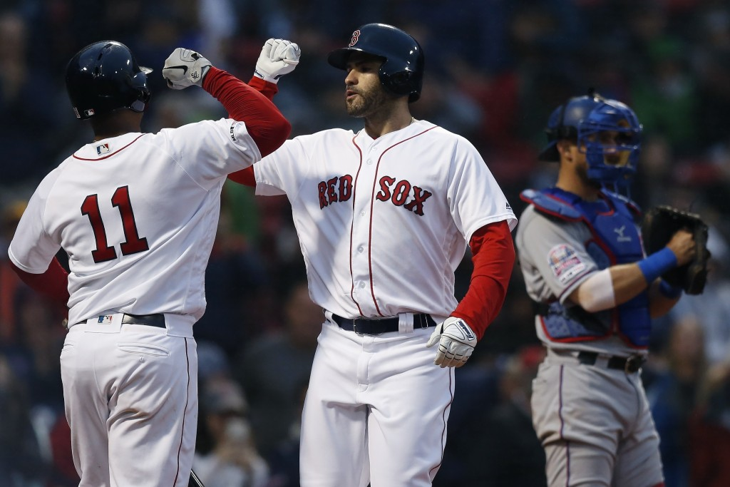 Boston Red Sox's J.D. Martinez, center, celebrates his solo home with teammate Rafael Devers (11) as Texas Rangers' Jeff Mathis, right, stands at home