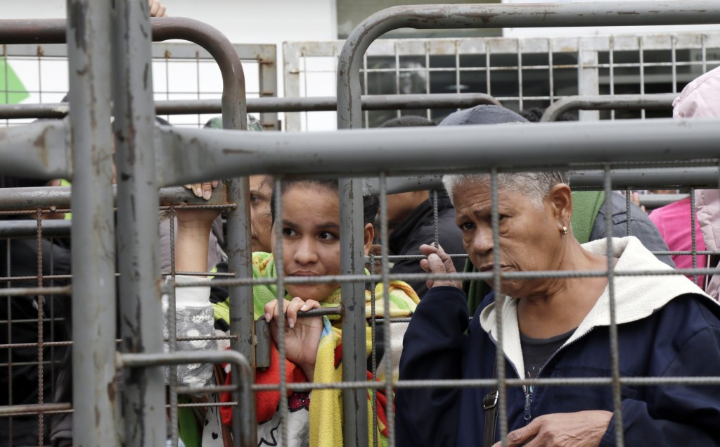 Venezuelans look though the fence at an immigration processing office on the Rumichaca bridge, after crossing the border from Colombia to Ecuador, Thu