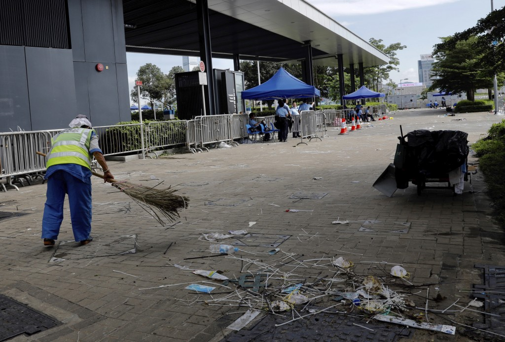 A worker cleans up in the aftermath of Wednesday's violent protest against the proposed amendments to extradition law near the Legislative Council in