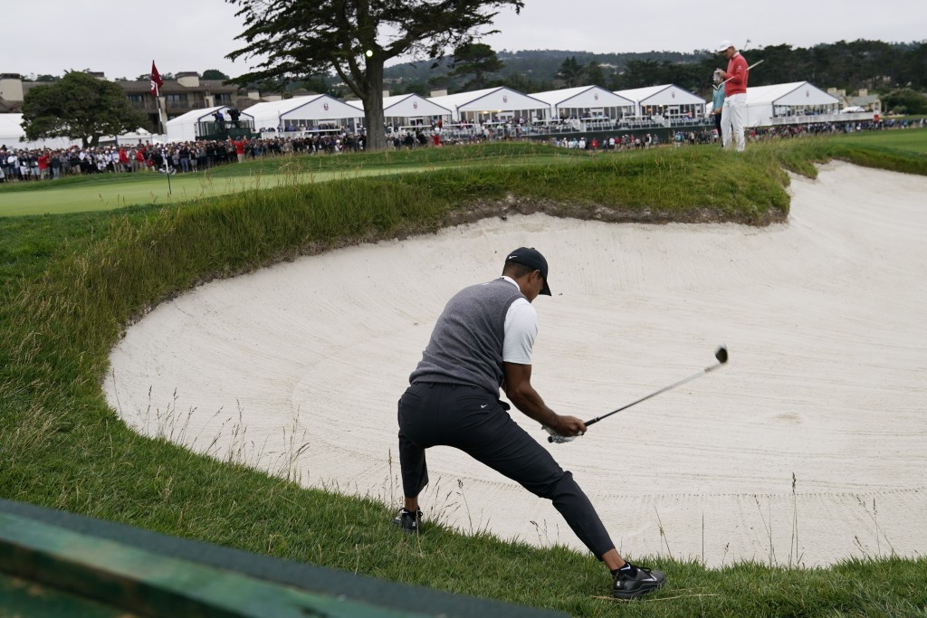 Tiger Woods hits out of the bunker on the 18th hole during the first round of the U.S. Open Championship golf tournament Thursday, June 13, 2019, in P