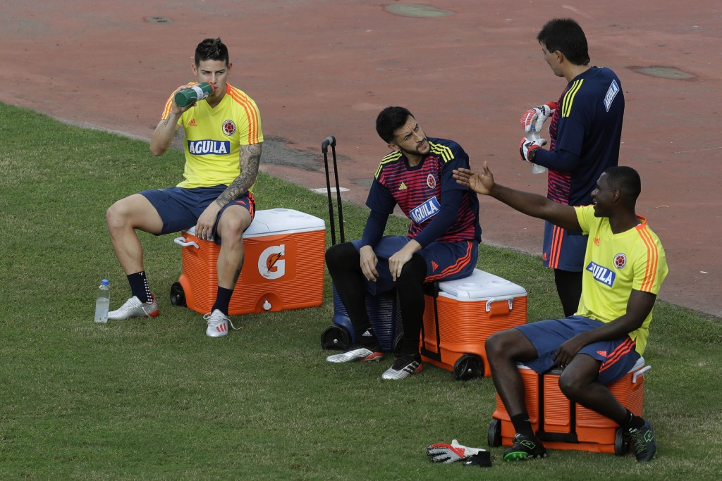 Colombia's James Rodriguez, left, drinks water before a training session of the national soccer team, in Pituacu stadium, in Salvador, Brazil, Thursda