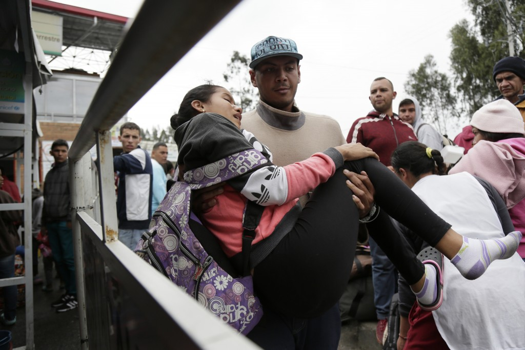 A woman who collapsed is carried by her husband, on the Rumichaca bridge, before crossing the border from Colombia to Ecuador, Thursday, June 13, 2019