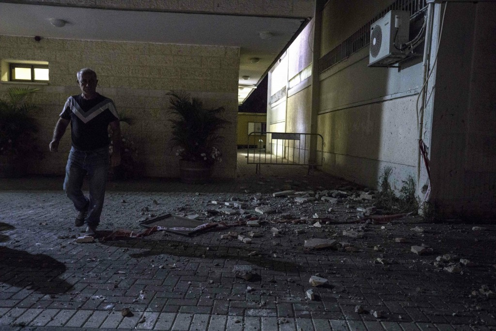 A man stands outside a Jewish religious school in Sderot, Israel, after it was hit by a rocket fired from the Gaza Strip, Thursday, June 13, 2019. (AP