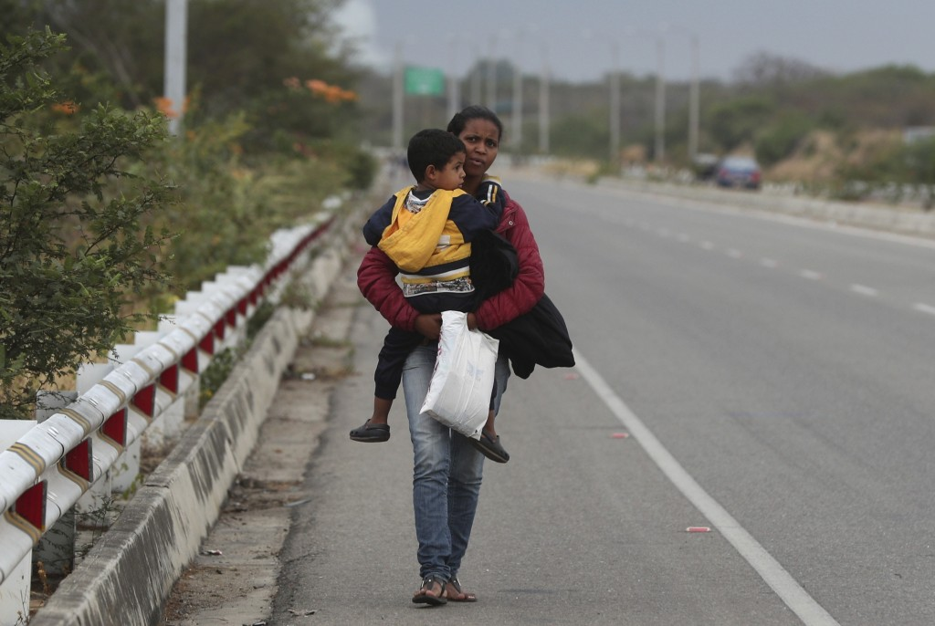 Venezuelan migrant Mary Ortega carries her son as she walks on the Pan-American Highway, after crossing the border Peru - Ecuador border, in Tumbes, P