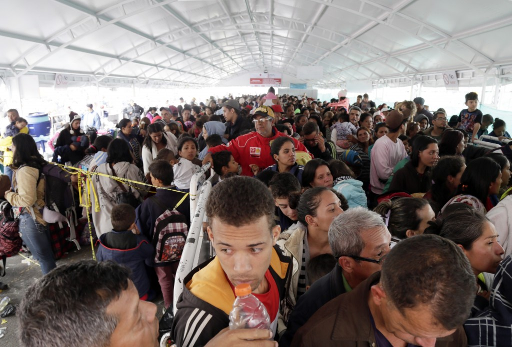 Venezuelans line up at an immigration processing office on the Rumichaca bridge, before crossing the border from Colombia to Ecuador, Thursday, June 1