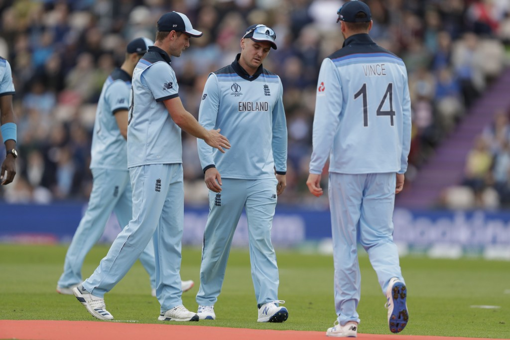 England's Jason Roy, centre, walks off the field of play with a leg injury during the Cricket World Cup match between England and West Indies at the H...