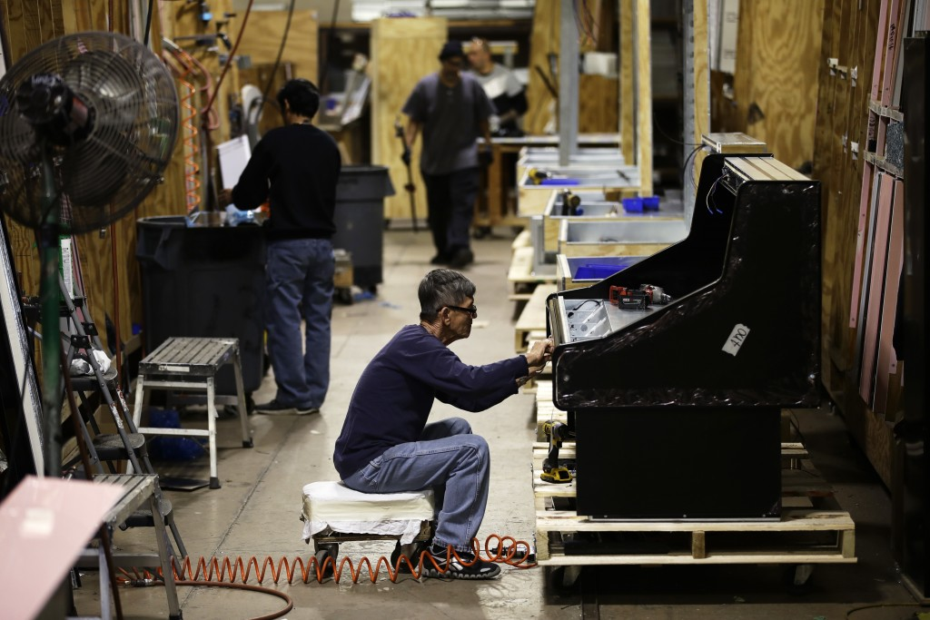 FILE - In this Oct. 18, 2018, file photo workers build refrigerators at the Howard McCray's commercial refrigeration manufacturing facility in Philade...