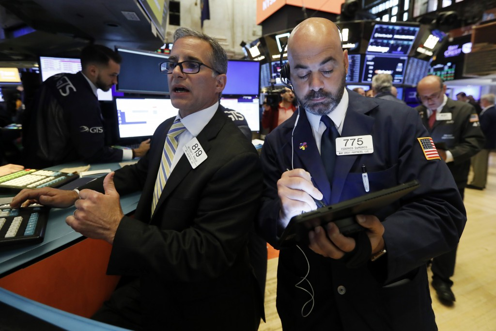 FILE - In this June 6, 2019, file photo specialist Anthony Rinaldi, left, and trader Fred DeMarco work on the floor of the New York Stock Exchange. Th