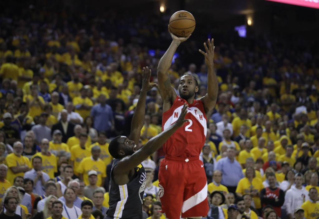 Toronto Raptors' Kawhi Leonard, right, shoots over Golden State Warriors' Draymond Green in the second quarter of Game 6 of basketball's NBA Finals Th