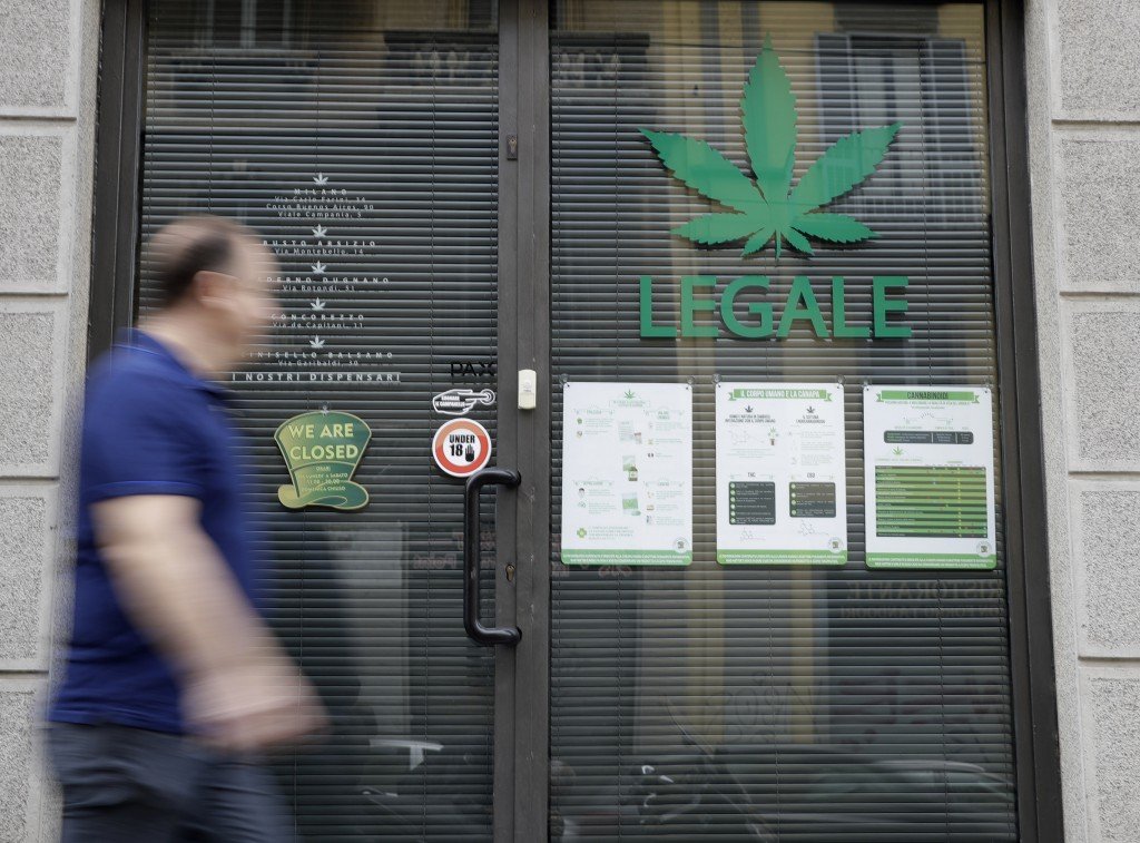 "In this Thursday, June 6, 2019 photo a man walks by the entrance of a cannabis light store, in which writing reads ""Legal"" on the shop window, in Mila..."