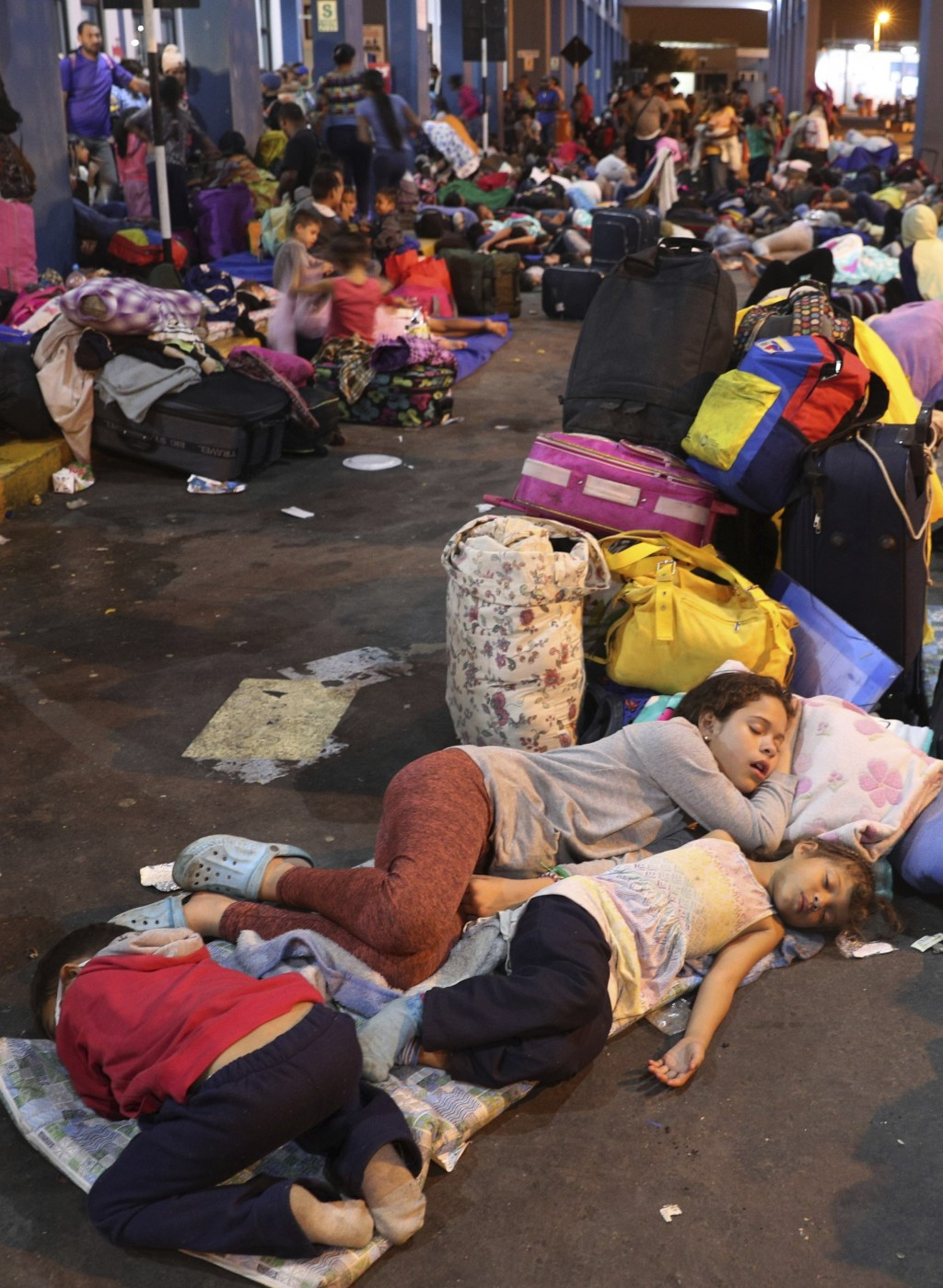 Venezuelan migrant children sleep while waiting with their parents to pass migration controls before the deadline on new regulations that demand passp