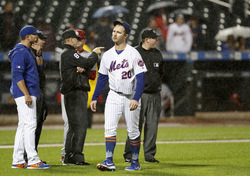 New York Mets manager Mickey Callaway, left, discusses field conditions with home plate umpire Mike Ripperger, second from left, and first base umpire