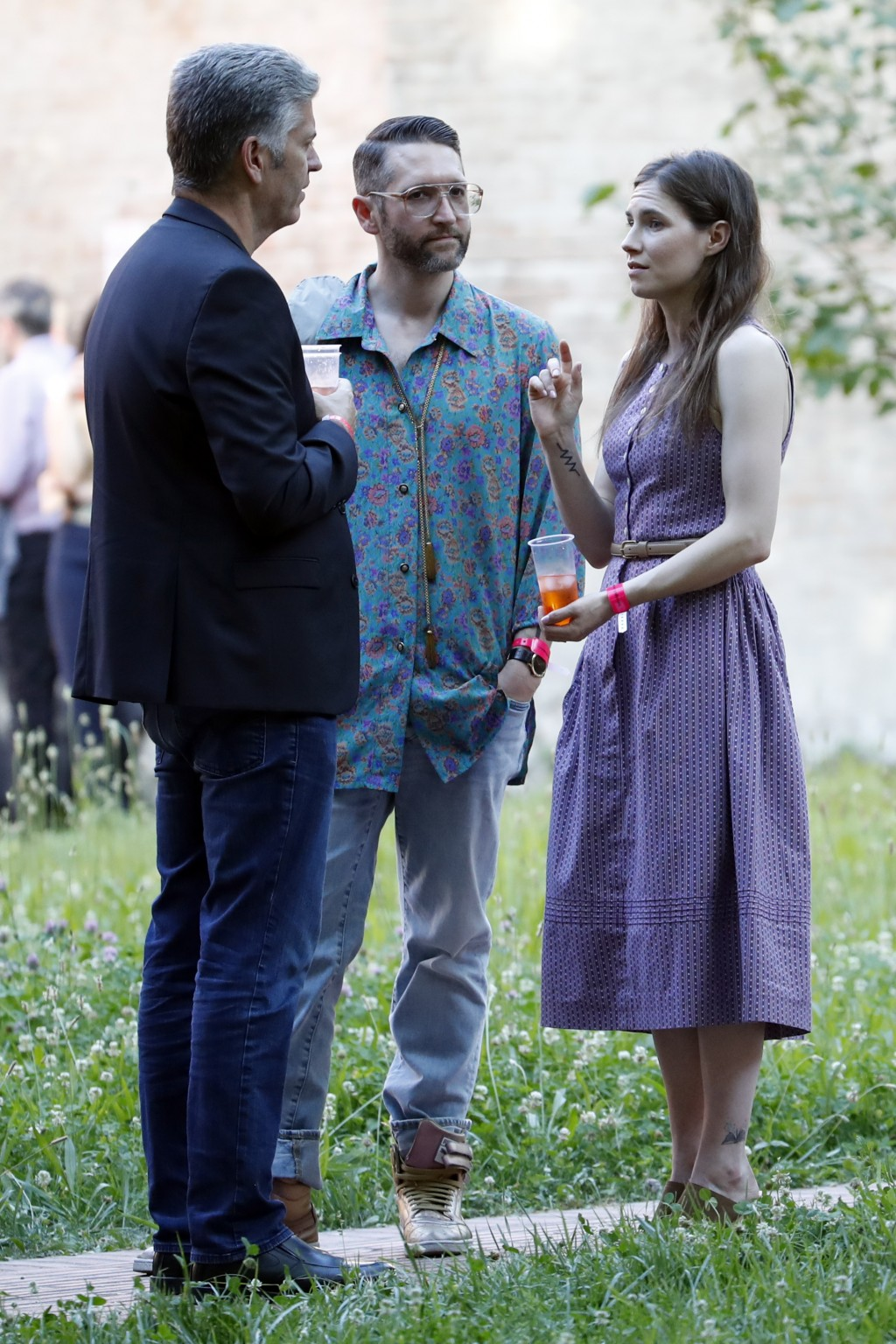 Amanda Knox, right, and her boyfriend Christopher Robinson, center, talk with a guest as they attend a cocktail for the opening of the Innocence Proje...