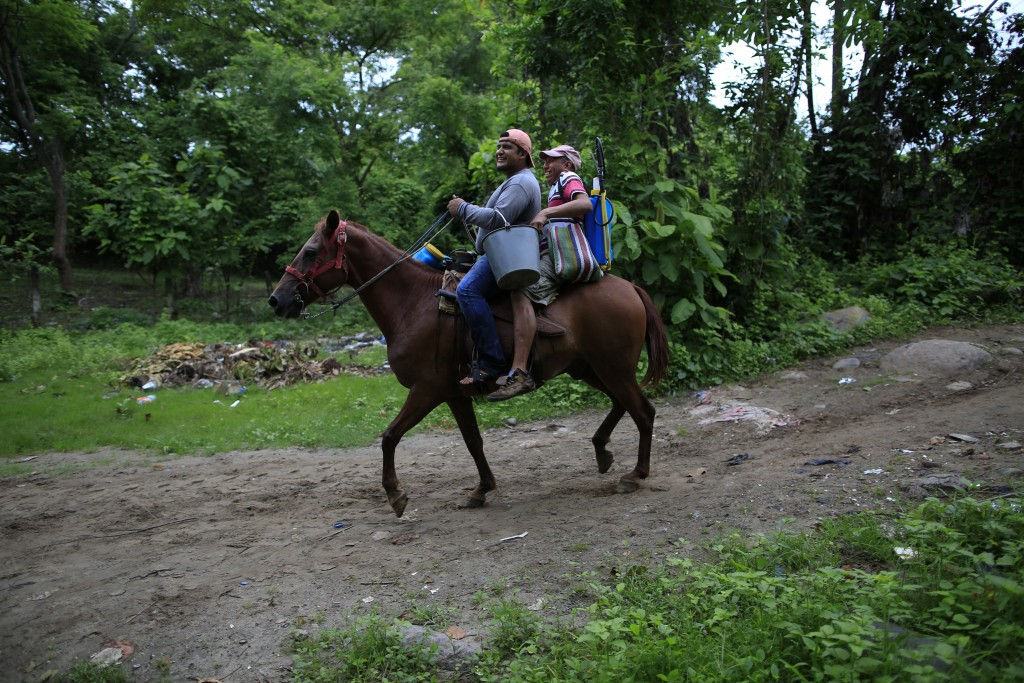 Carrying backpack sprayers and headed to work on a local farm, Artemio Lopez, right, and another man ride a horse as they arrive in Frontera Hidalgo,