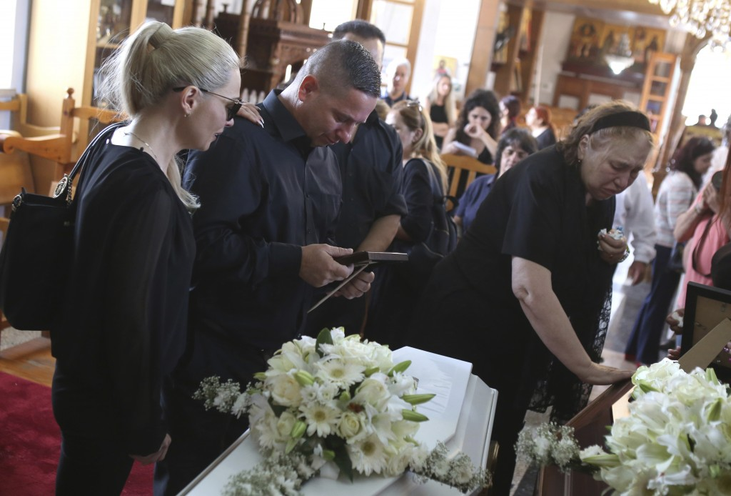 Relatives mourn over the coffins of Livia Florentian Bunea, 36, from Romania and her eight year-old daughter Elena Natalia at a church in the village