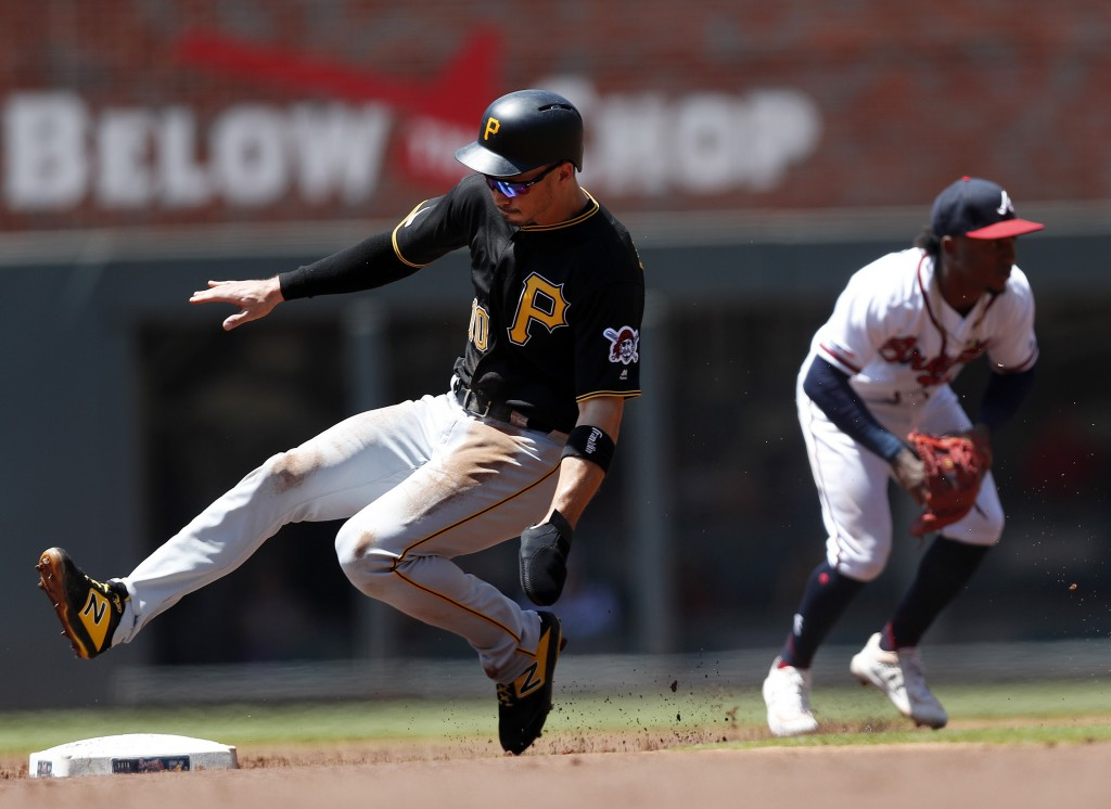 Pittsburgh Pirates' Bryan Reynolds (10) advances to second base as Atlanta Braves second baseman Ozzie Albies (1) fields a ground ball from Starling M