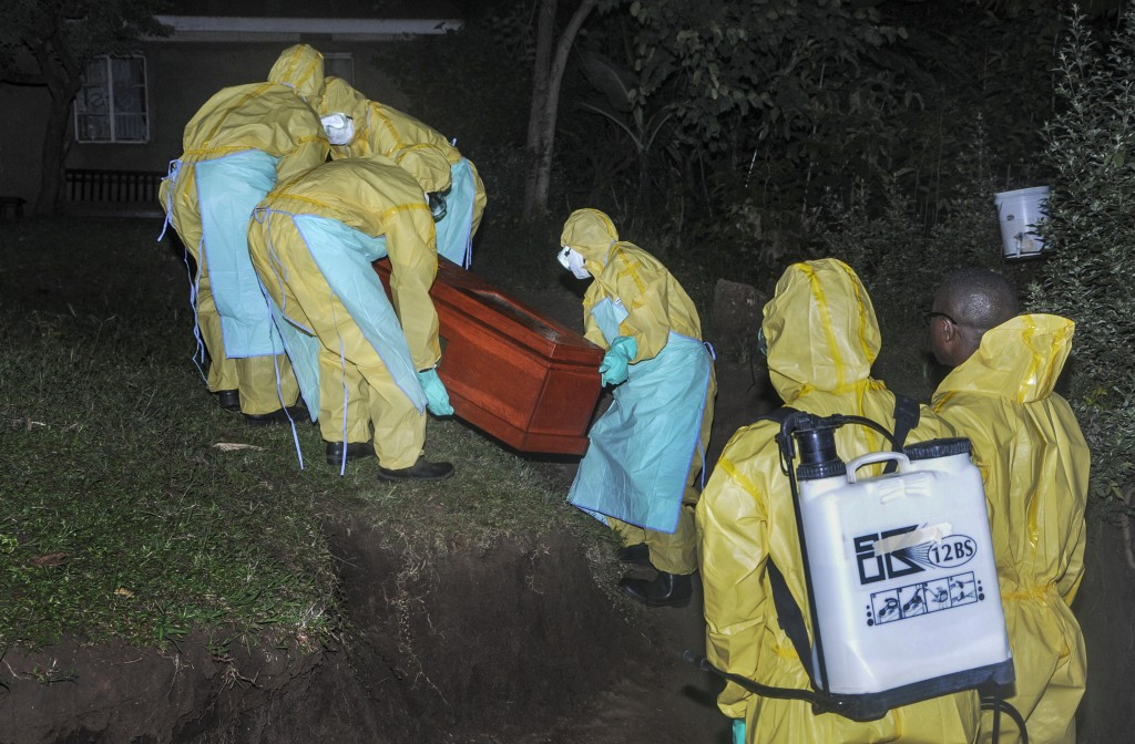 Workers wearing protective clothing bury Agnes Mbambu who died of Ebola, the 50-year-old grandmother of the 5-year-old boy who became Ebola's first cr