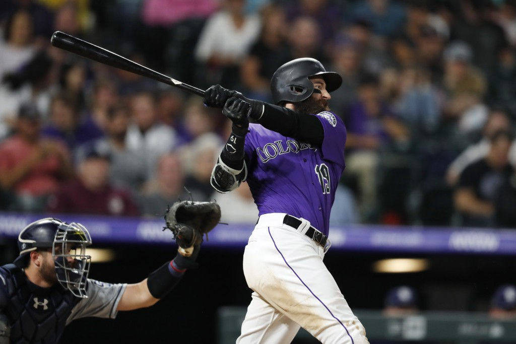 Colorado Rockies' Charlie Blackmon watches his solo home run next to San Diego Padres catcher Austin Allen during the sixth inning of a baseball game