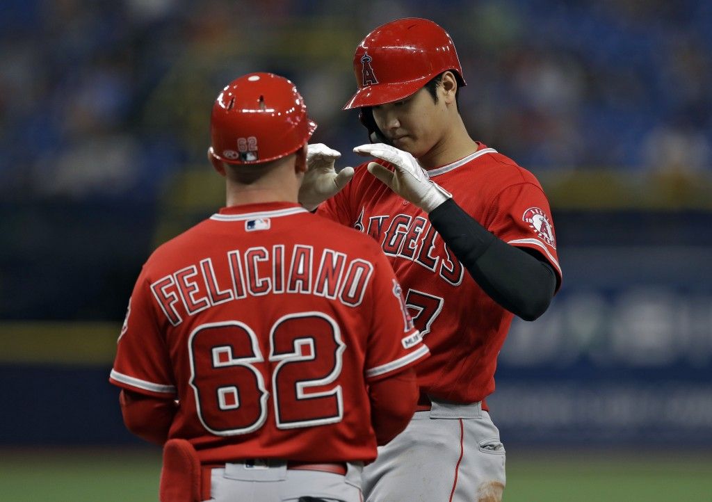 Los Angeles Angels' Shohei Ohtani, right, of Japan, celebrates with first base coach Jesus Feliciano after his single off Tampa Bay Rays' Hunter Wood,