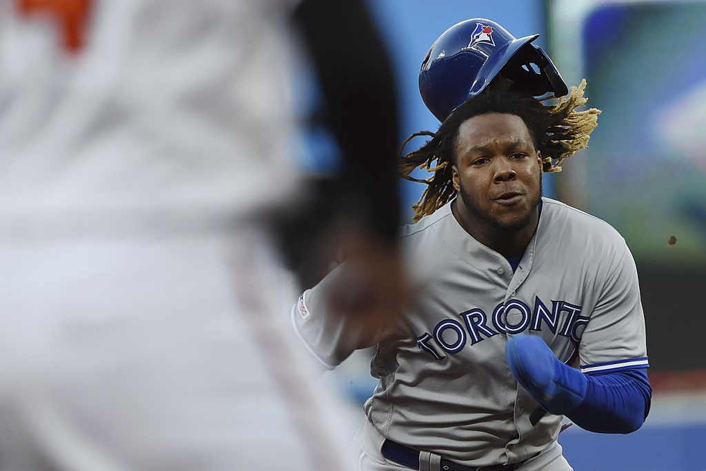 Toronto Blue Jays' Vladimir Guerrero advances to third after tagging up on a fly ball during the first inning of the team's baseball game against the