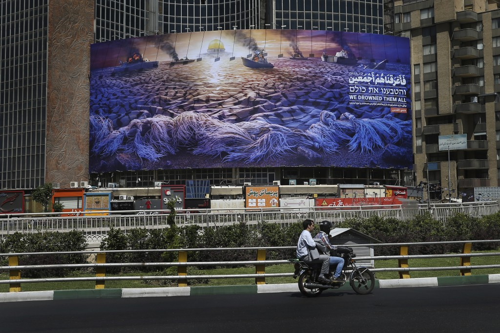 In this Wednesday, May 29, 2019 photo, People drive at Vali-e-Asr Square in downtown Tehran where an anti-Israeli billboard is place ahead of the Al-Q