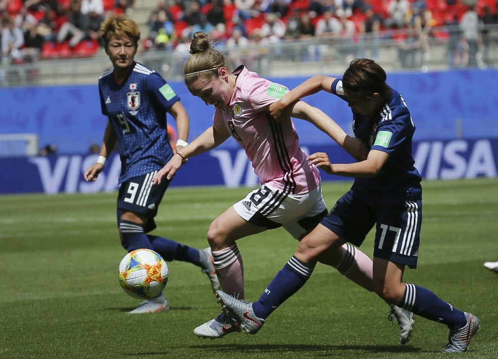 Scotland's Kim Little, center, vies for the ball with Japan's Narumi Miura, right, and Japan's Yuika Sugasawa, left, during the Women's World Cup Grou...