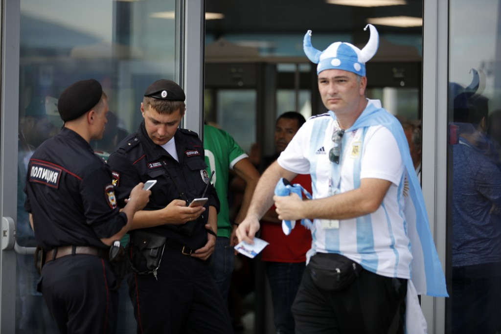 FILE - In this June 17, 2018, file photo, a soccer fan walks past two Russian police officers as they control an entrance ahead of the group F match b