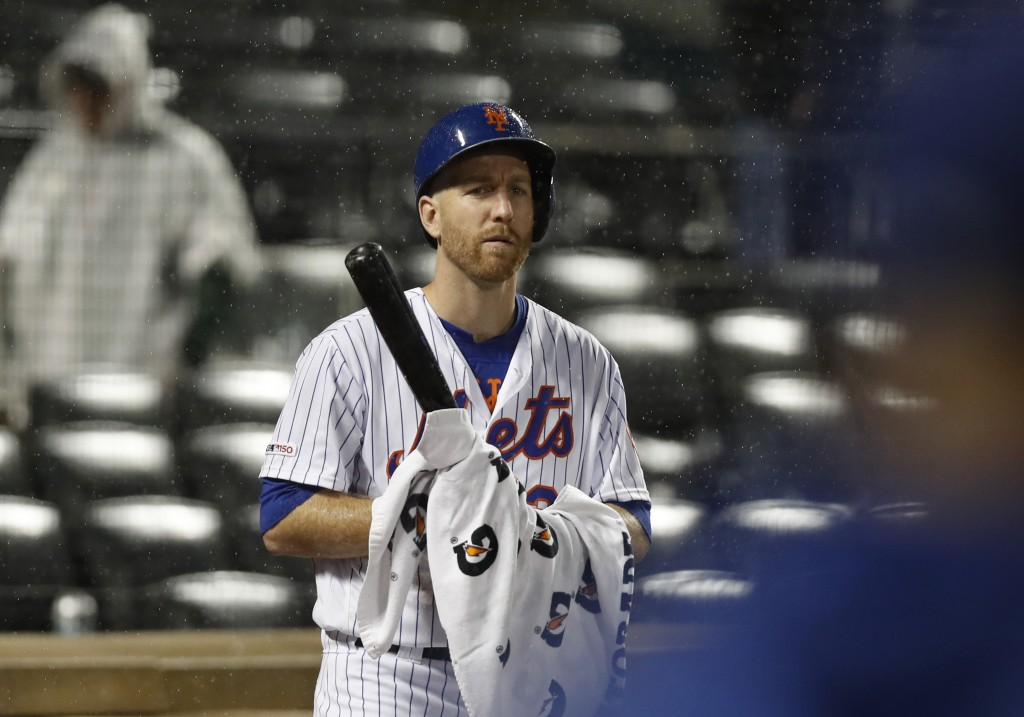 New York Mets' Todd Frazier wipes his bat with a towel as he looks for the call from his manager moments before the team's baseball game against the S...