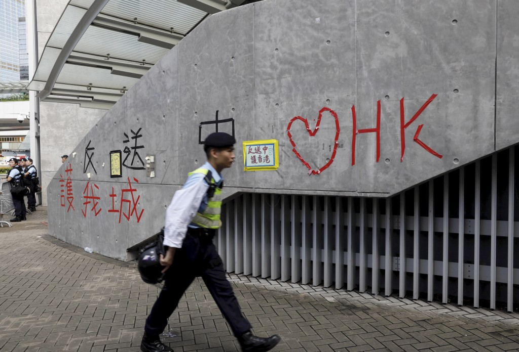 "A police officer passes by ""Love Hong Kong"" words formed with tape near the Legislative Council in Hong Kong on Friday, June 14, 2019. Calm appeared t"