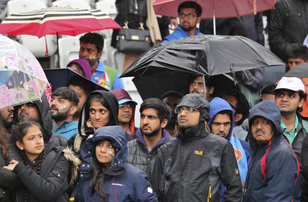 Fans wait to have a glimpse of Indian players before the Cricket World Cup match between India and New Zealand was abandoned due to rain at Trent Brid
