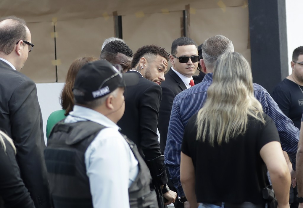 Brazilian soccer star Neymar, center, arrives to a police station to testify, after a woman accused him of rape, in Sao Paulo, Brazil, Thursday, June