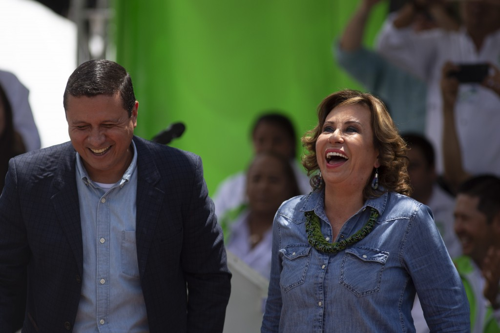 Sandra Torres, presidential candidate of the National Unity of Hope party, UNE, right, and her running mate Carlos Raul Morales laugh during their clo
